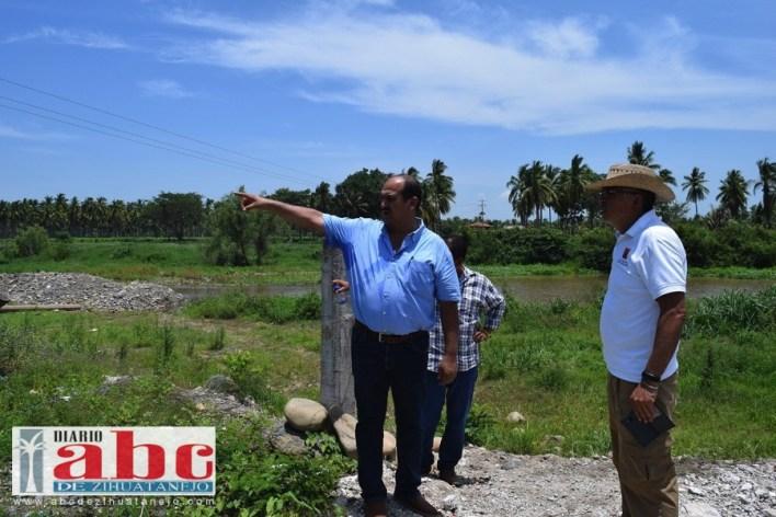 El presidente Arturo Gómez muestra al personal de Protección Civil Estatal los puntos de riesgo para los habitantes de Petatlán ubicados sobre la ribera del río.