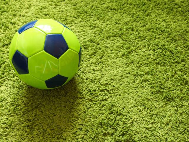 Football (Soccer) ball on a green surface imitating artificial grass. Sports photography; Shutterstock ID 1034235352