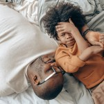 Canva - Ethnic dad and kid resting together on bed