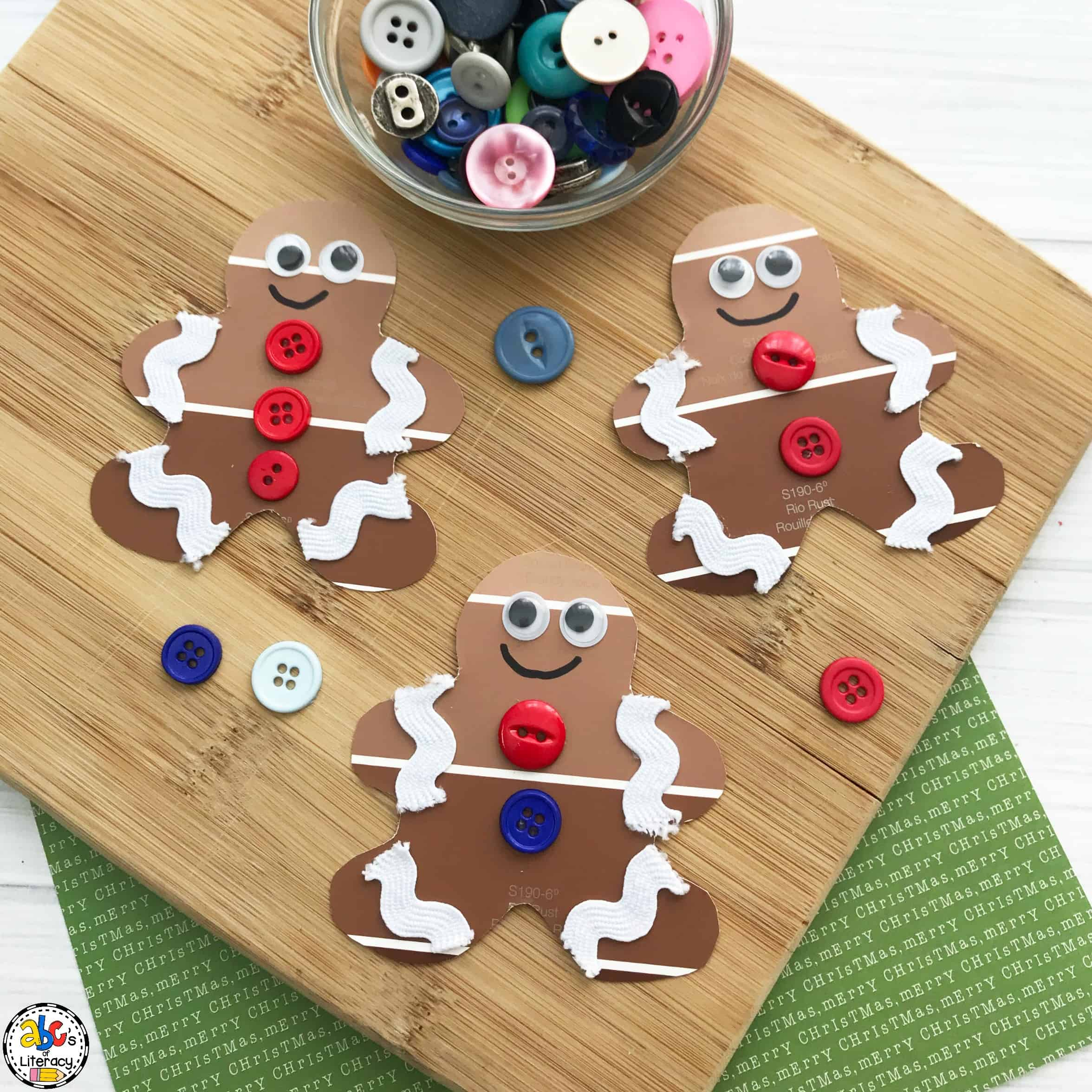 paint chip gingerbread craft on wooden board with jar of buttons nearby