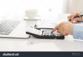 stock-photo-businessman-using-a-calculator-to-calculate-the-numbers-accounting-accountancy-calculation-403855180