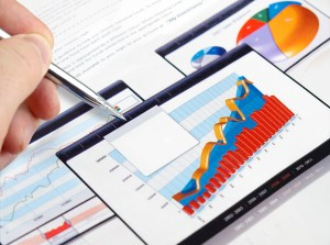 Foto de uma mão mexendo em alguns gráficos, representando o planejamento financeiro