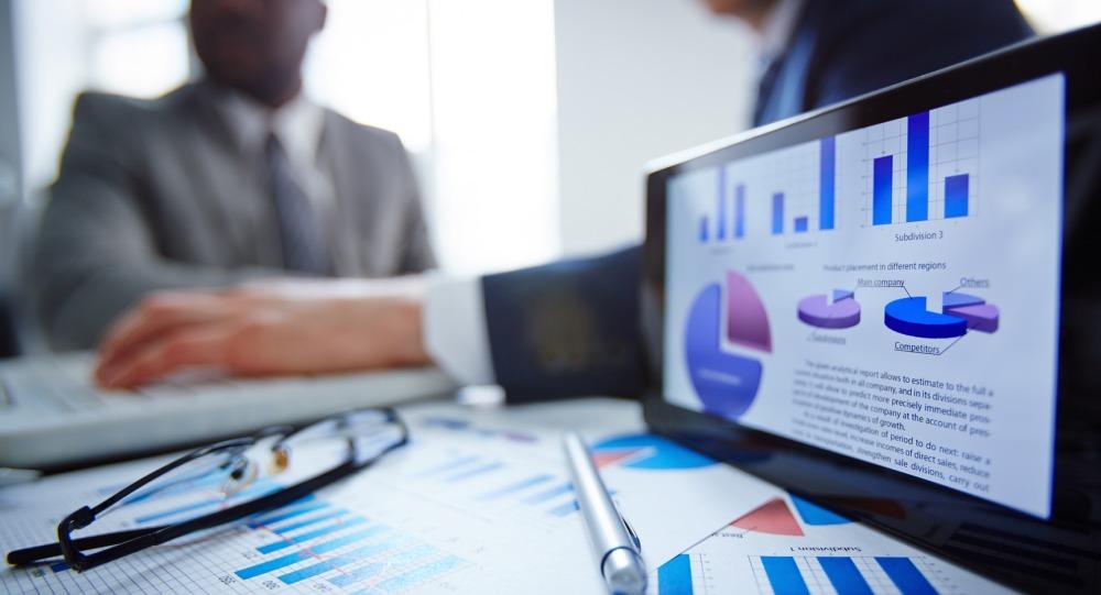 Foto de um tablet com diversos gráficos, papeis, uma caneta óculos em cima de uma mesa, com dois homens ao fundo representando a pesquisa para PMEs