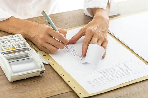 Foto de uma mão anotando em um bloco e com uma calculadora anotando os erros em notas fiscais