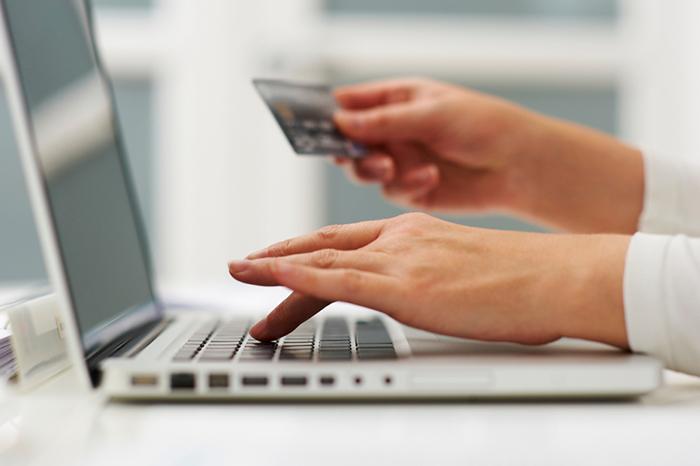 Foto de uma pessoa digitando em um notebook e na outra mão segurando um cartão, representando os tipos de nota fiscal eletrônica