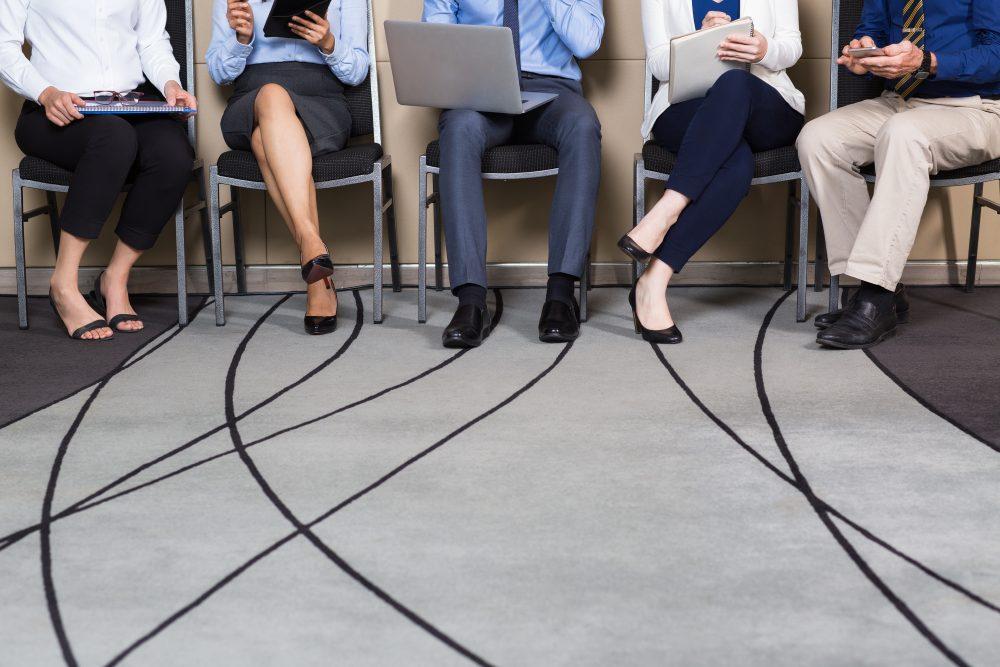 Foto de algumas pessoas sentadas em uma sala, mostrando apenas seus pés, demonstrando a importância do setor de rh