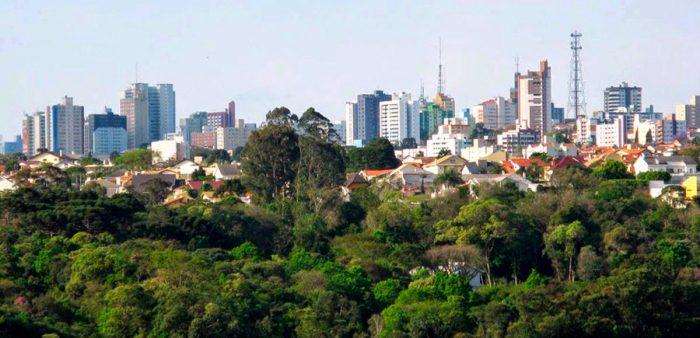 Foto da vista da cidade, com algumas árvores em primeiro plano, e muitos prédios ao fundo, representando abrir empresa em Ponta Grossa