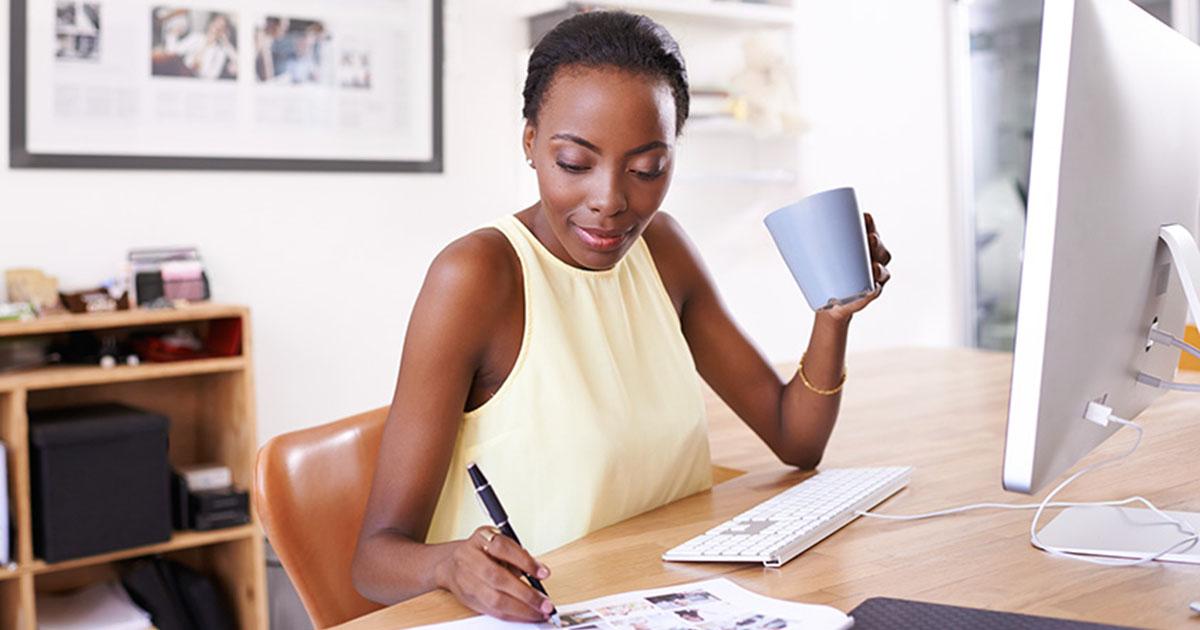 Foto de uma mulher trabalhando de casa, bebendo café e fazendo anotações, representando o número de empresas criadas