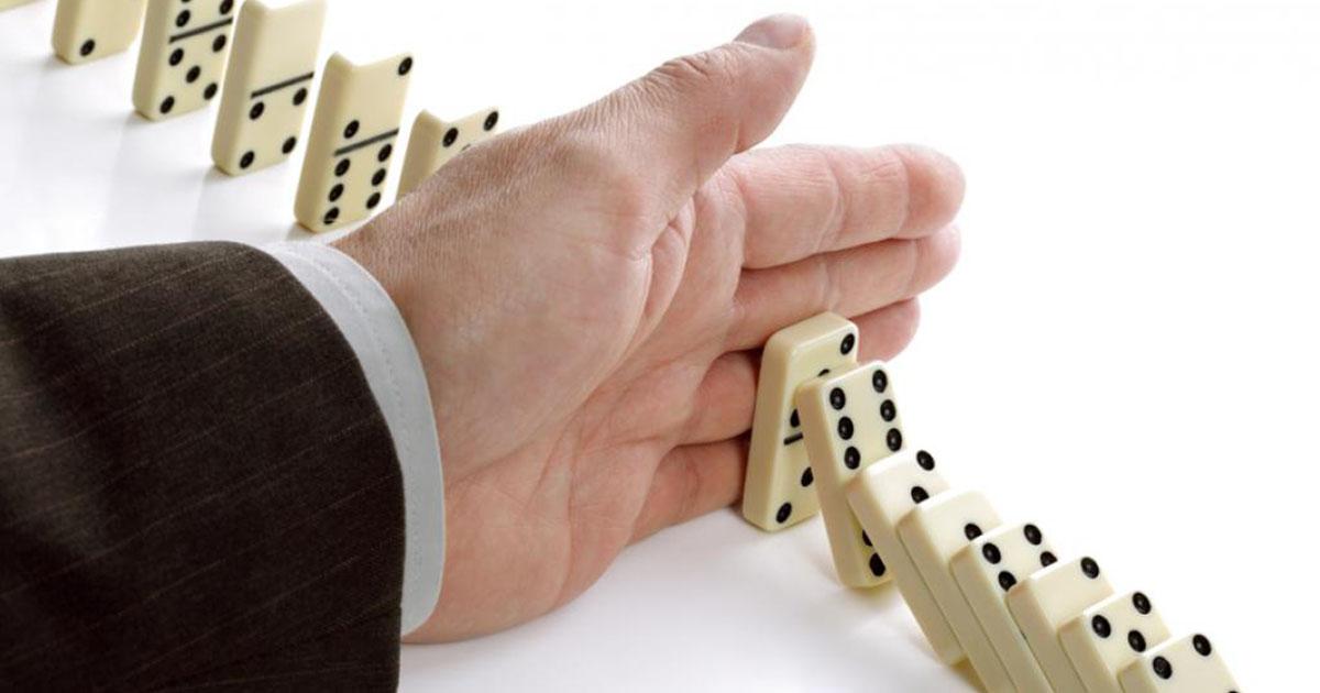Foto de uma mão masculina parando uma sequência de peças de dominó, representando a gestão de crise