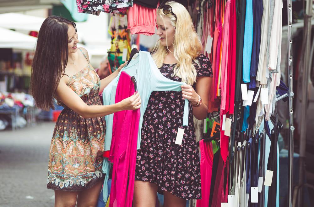 foto de duas mulheres experimentando roupas, representando como abrir um brechó