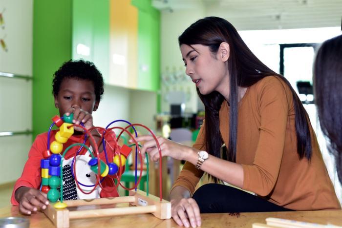 Foto de uma mulher e uma criança brincando, representando como abrir uma brinquedoteca