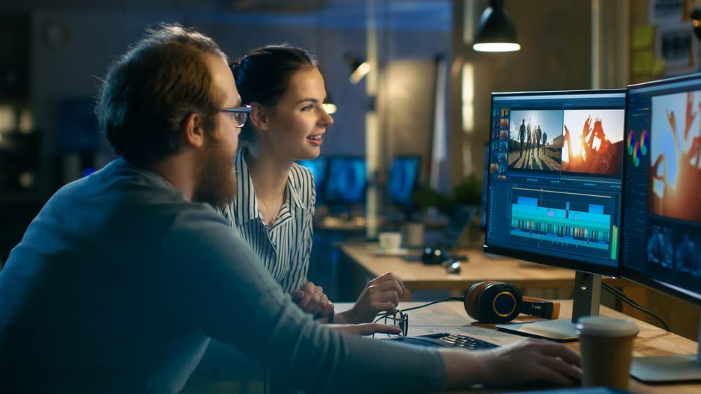 Foto de duas pessoas analisando uma gravação no computador, representando como abrir uma produtora audiovisual