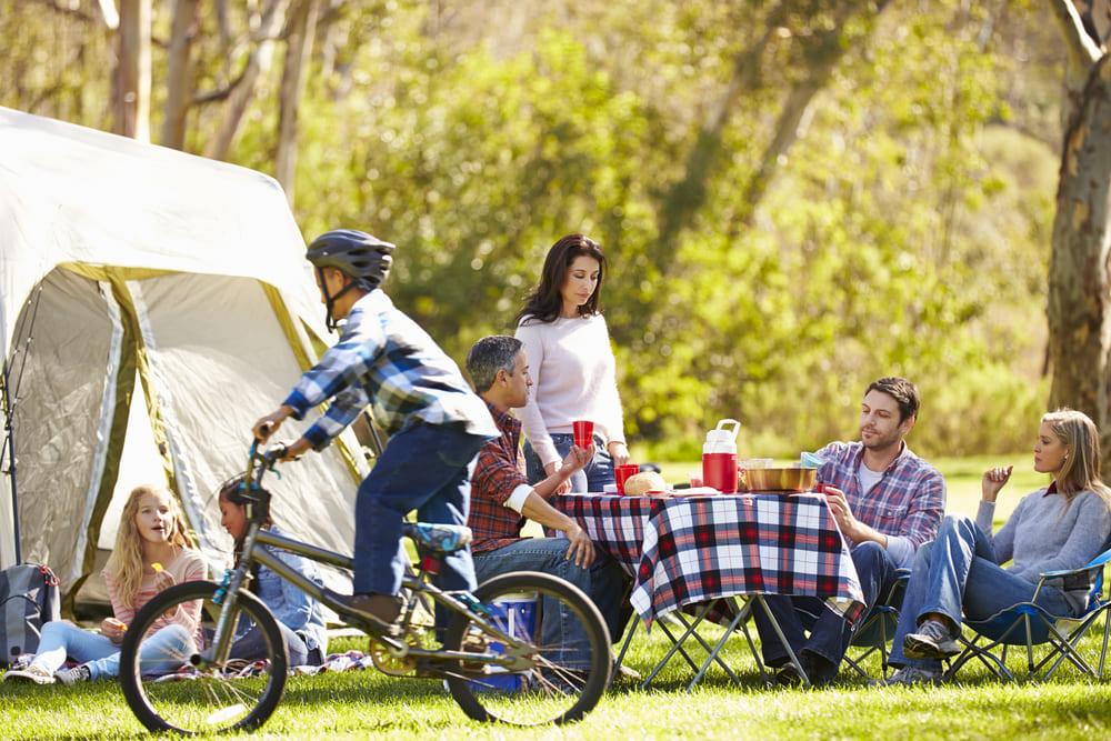 foto de uma família reunida e um menino andando de bicicleta, representando como montar um camping