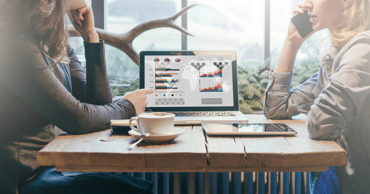 Foto de duas mulheres analisando dados em um notebook, representando empreender em guapimirim