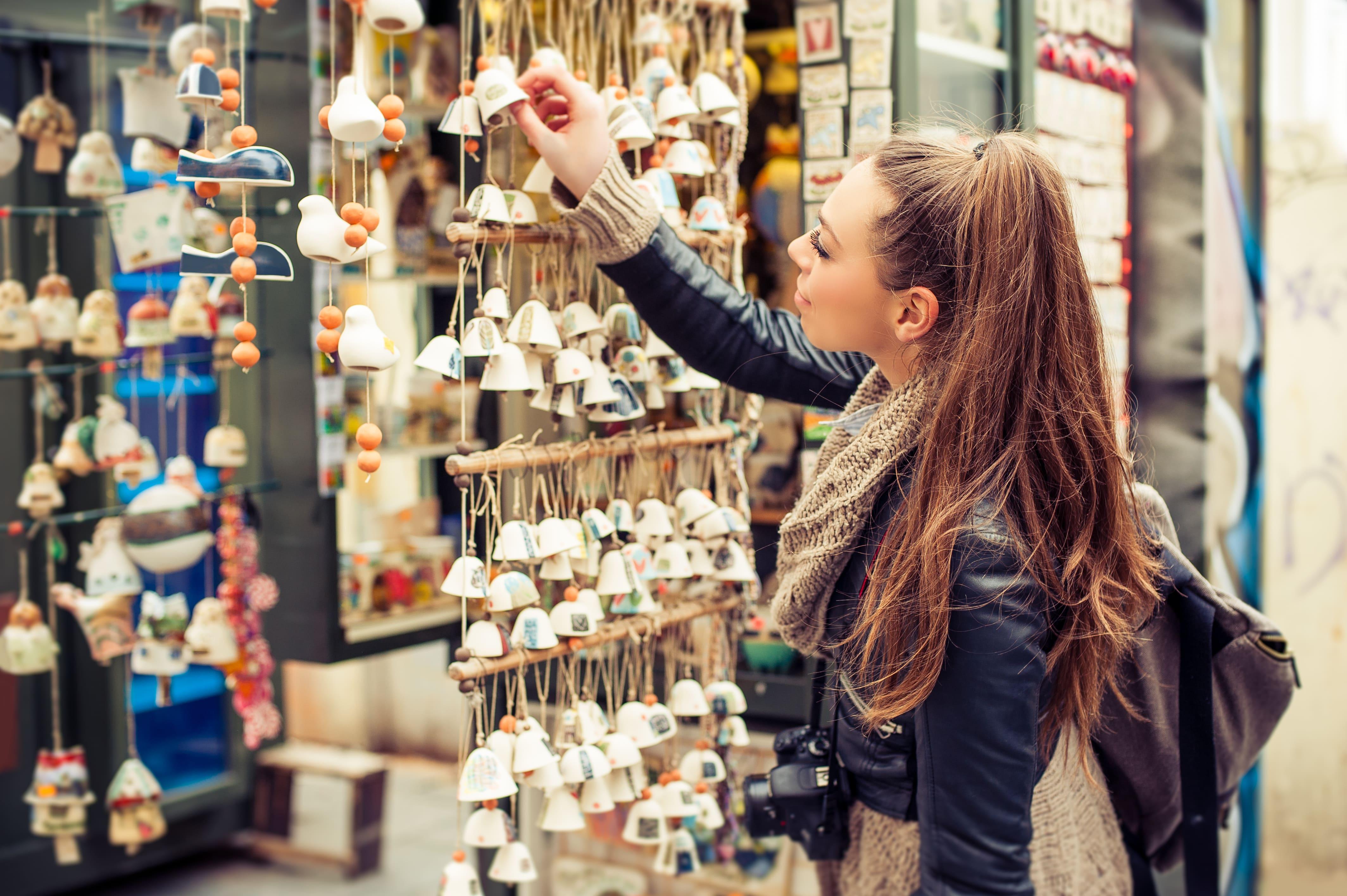 Imagem de uma mulher que está viajando e parou em uma loja para inspirar o empreendedor que deseja abrir uma loja de souvenirs