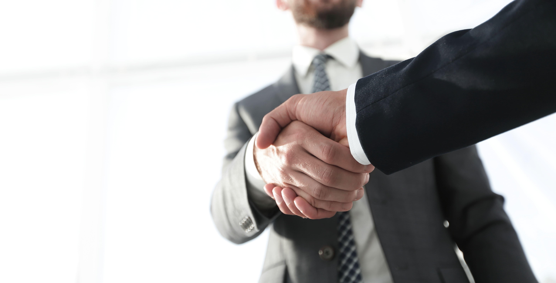 Imagem de dois rapazes apertando a mão um do outro para selar o negócio que vão empreender em Urupês
