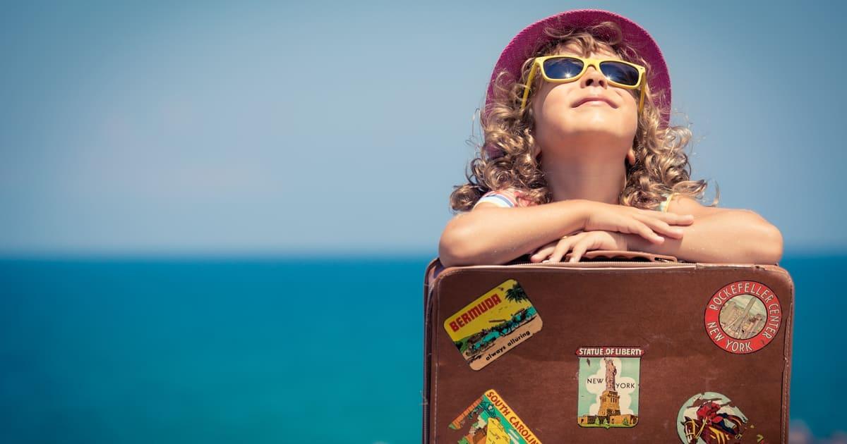 Imagem de uma criança com malas para inspirar ao empreendedor que deseja montar uma colônia de férias