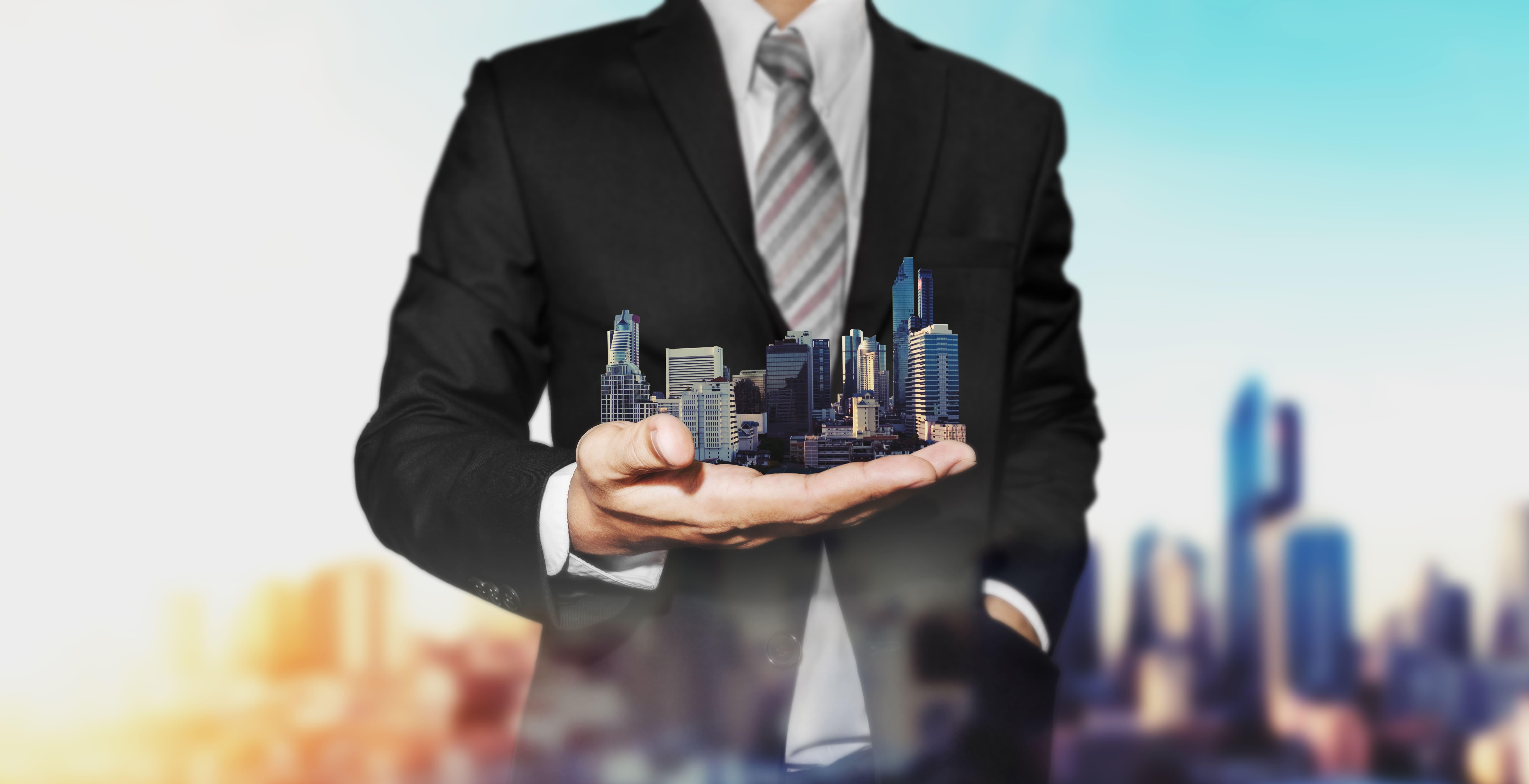 Imagem de um homem com vários condomínios na mão para remeter o empreendedor que vai montar um serviço de administração de condomínios