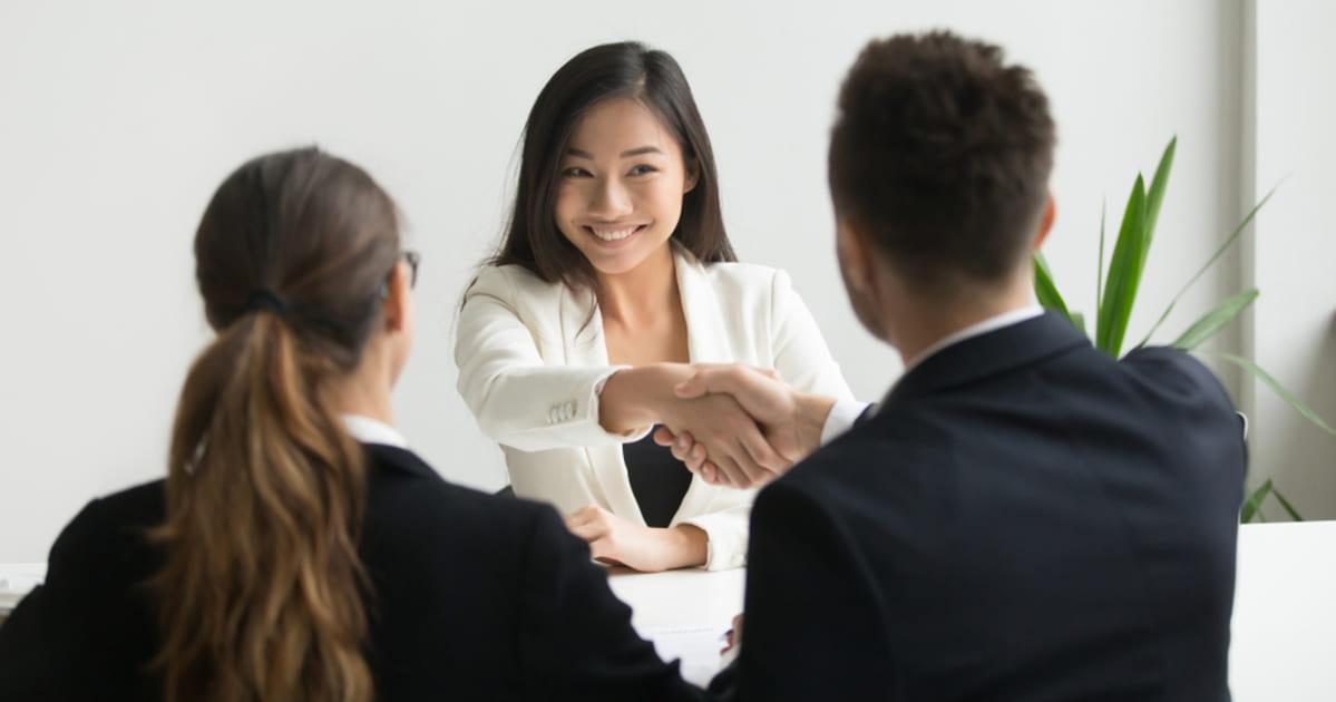 foto de uma mulher cumprimentando um homem, representando como contratar um funcionário