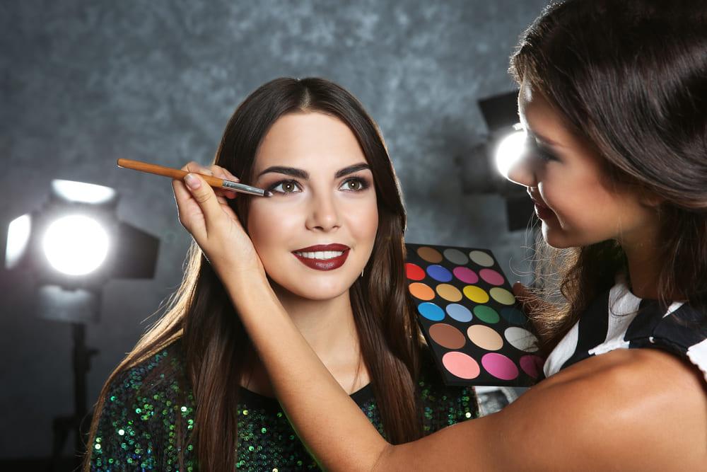 foto de uma mulher maquiando outra, representando como ter mei para maquiadora profissional
