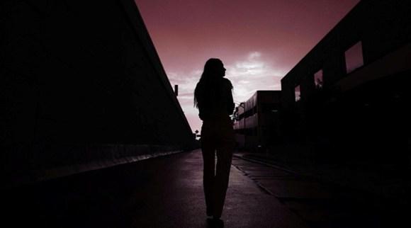 Mulher solitária observa vagão com o entardecer ao fundo