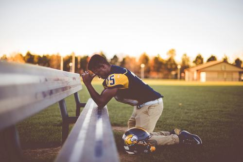 Picture of football player kneeling.