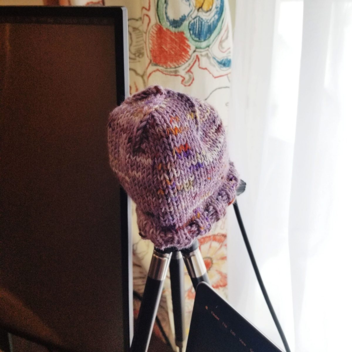 A tiny knitted hat covering a webcam on a tripod mount on Abbie's desk. The yarns are light purple and a hand-dyed cream-mauve-rust, held double.