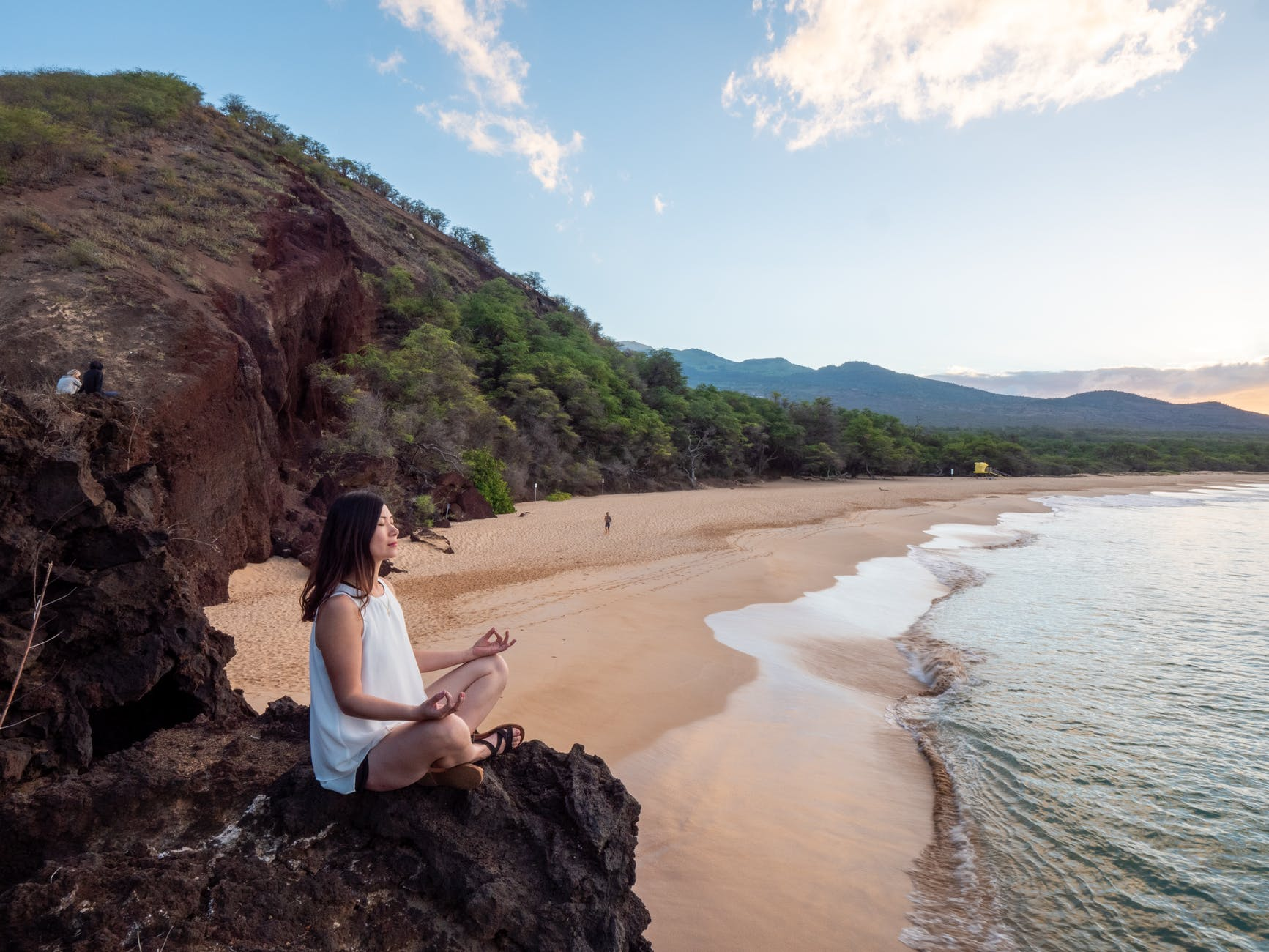 young ethnic woman meditate on empty beach