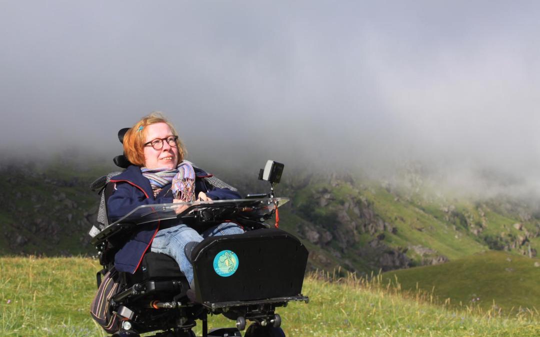 Anne Gersdorff im Rollstuhl vor einem nebelverhangenen Berg auf einer grünen Wiese