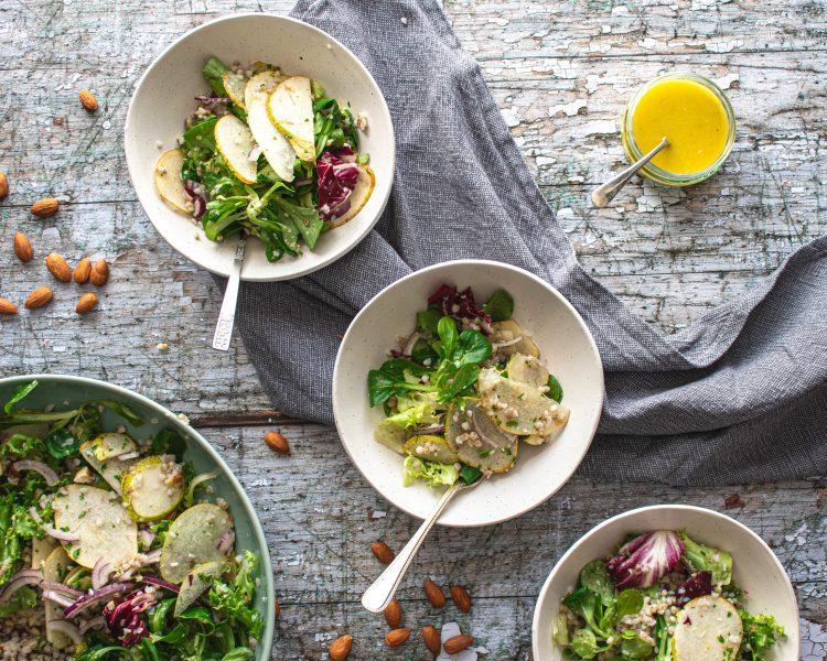 3 small salad bowls, 1 large salad bowl and a bowl of dressing