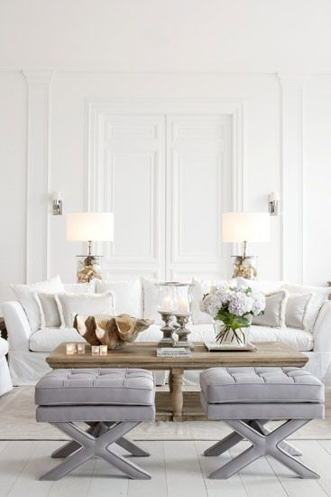 How to decorate with neutral colors: this all-white living room doesn't look the leave bit intimidating with those stunning pewter grey ottomans and gorgeous weathered wood coffee table!