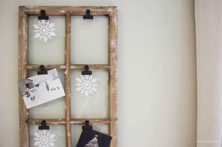 Use an old window and some clips to create a one-of-a-king Christmas card display. It makes for a beautiful decor piece in your home! See it all on https://ablissfulnest.com/ #Christmas #CHristmasCards #VintageDecor
