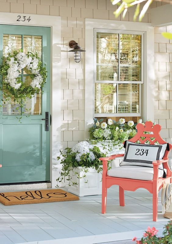 Love the color pops on this spring front porch! A light turquoise wooden door is decorated with a white and green floral wreath. A bright coral colored deck chair sits with white fabric throw pillows and curtains. The floral arrangements are a mix or white and green flowers. #spring #springporch #springdecorating #springfrontporch