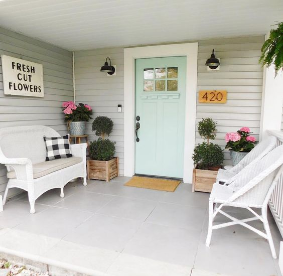 """Love the fresh colors of this spring front porch! This porch has a mint green painted front door. On either side, wooden planter boxes hold green shrubs and bright pink flowers. Wicker porch furniture is decorated with black and white flannel throw pillows. A wooden sign hanging on the wall says """"fresh cut flowers"""". #spring #springporch #springdecorating #springfrontporch"""
