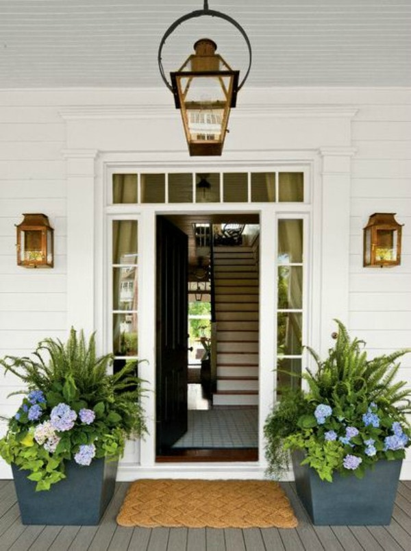 An open front door is flanked by two large square stone planters filled with tropical plants. Purple and blue flowers accent the green leaves.
