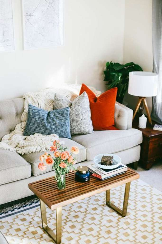 Mix your throw pillows with a soft throw blanket to add style to your couch like this soft knitted throw blanket on this gray cloth couch