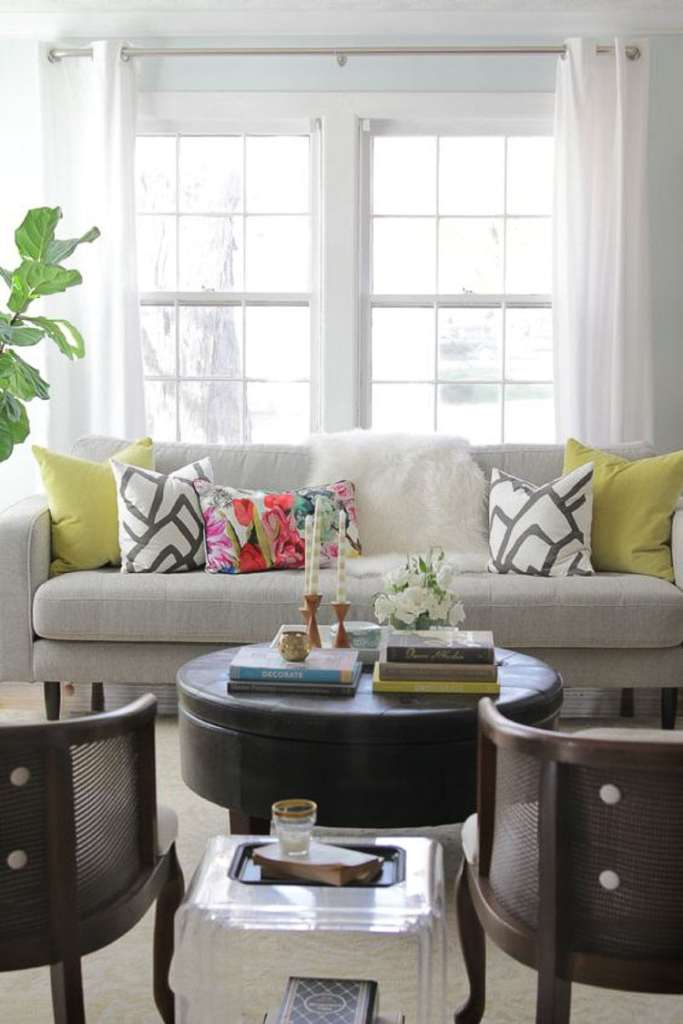The matching throw pillows on either side of the white throw blanket on this gray couch gives a very balanced look to this living room scene