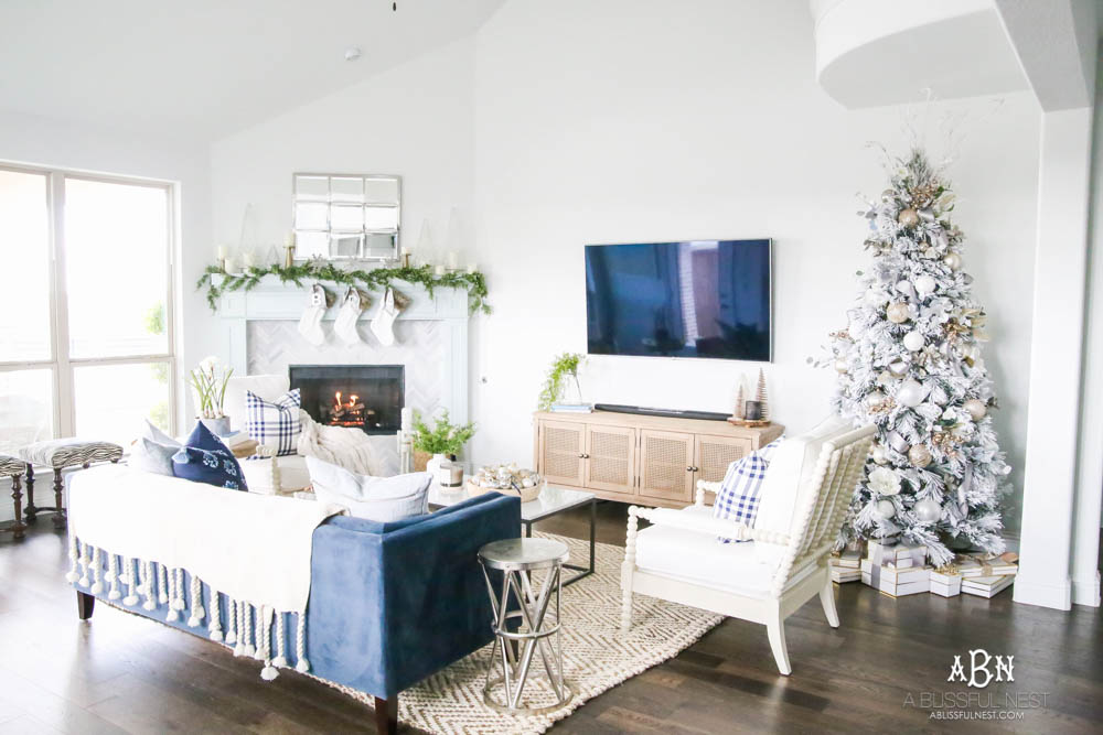Beautiful blue and silver Christmas living room decor in a bright white space with juniper garland and silver and blush ornaments. Check out all the white, silver and gold Christmas decor in this holiday home tour on ABlissfulNest.com. #ABlissfulNest #Christmasdecor #Christmasdecorating #CoastalChristmasdecor #christmastree #christmasmantle