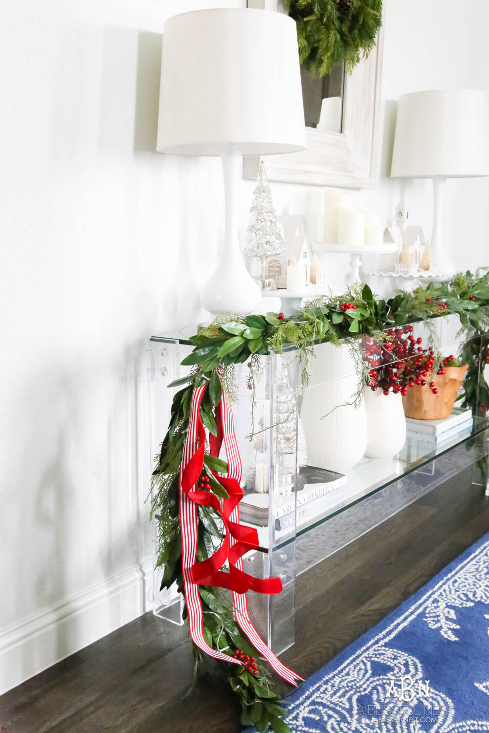 Layered garland makes a full look and adding in festive red and white ribbon. Love these easy and simple classic Christmas touches in this entryway. #christmasentryway #christmasentry #christmasentrydecor #christmasentrywayideas #christmashometour