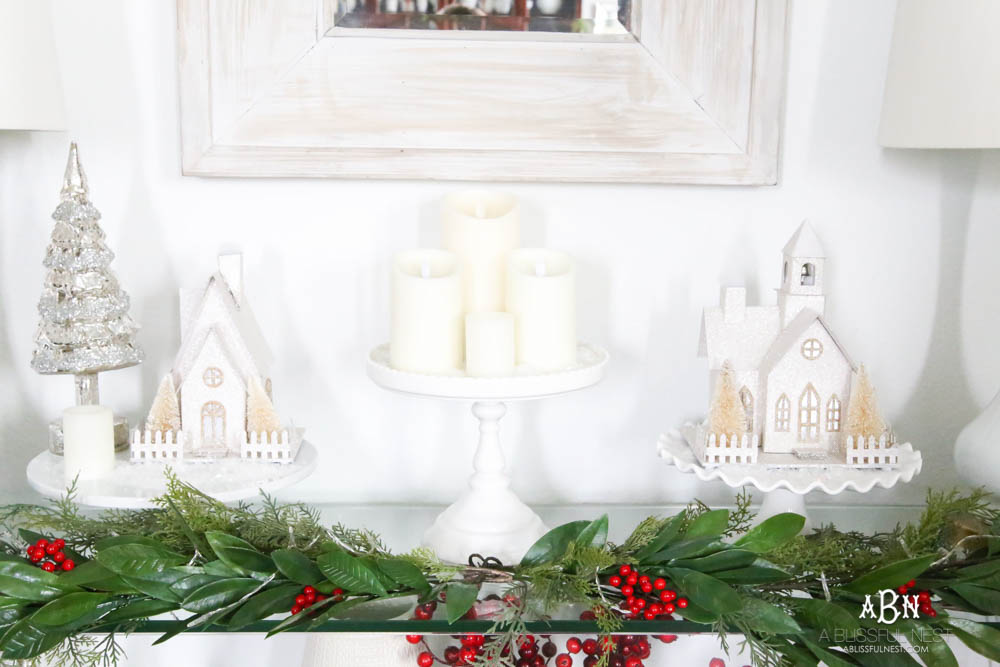 Use cake plates to add height to your display. I love the collection of candles and lighted glitter holiday houses sprinkled with snow for a beautiful simple classic Christmas look. #christmasentryway #christmasentry #christmasentrydecor #christmasentrywayideas #christmashometour