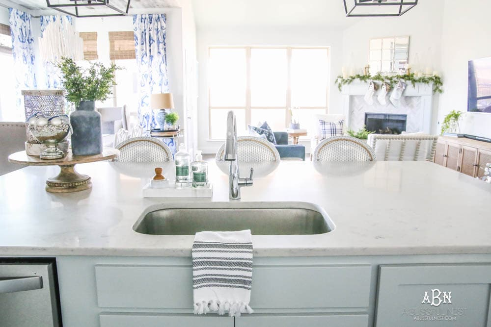 Blue and silver Christmas kitchen décor. All white kitchen with subtle holiday décor for a fresh coastal Christmas look. Mini wreaths on the backs of the barstools, beautiful bay leaf above the range. #christmaskitchen #christmashometour #holidayhometour #kitchenideas