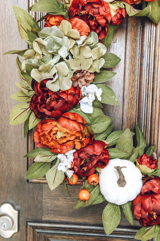 Beautiful burnt orange, muted green, mini pumpkins, hydrangea and small berries. Gorgeous fall wreath details. #ABlissfulNest #fallporch #fallinspiration