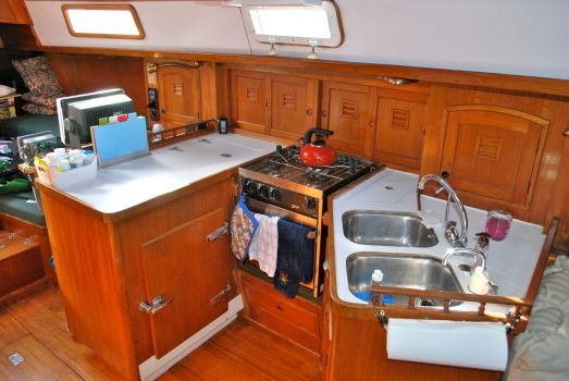 View aft of the galley showing the reefer, stove and dual sinks with plenty of cabinet storage