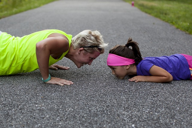 Mom and Daughter on the pavement doing pushups