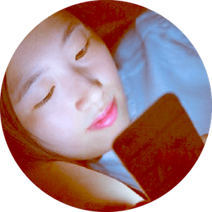 A teen girl with light skin and dark hair lays on her side while looking at phone screen. The screen illuminates her face in a dark room.