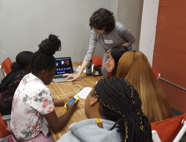 Six teen girls are seated around a table, looking at a laptop screen. A woman leans over the table and presses a button on the laptop.