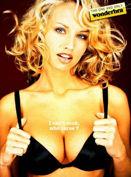 "Ad for Wonderbra from the 1990s probably: Blonde-haired white woman wearing a black bra. On her cleavage it says ""I can't cook. Who cares?"""