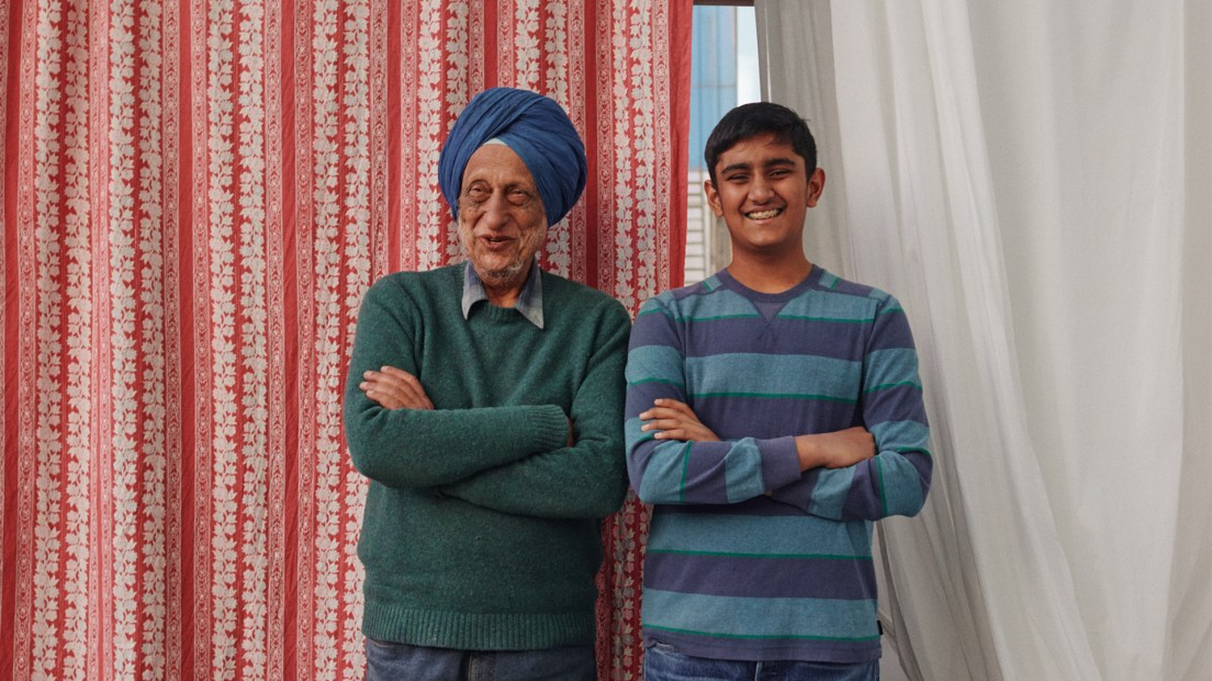 Father and son stand in front of textiles, smiling with arms folded