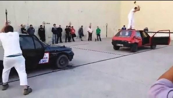 Dos aizkolaris navarros cortando sendos coches con el hacha