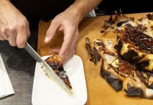 Chef Dave Beran cutting and plating a slice of a chilled burnt Basque cheesecake. (Ricardo DeAratanha / Los Angeles Times)